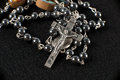 Crucifix rosary beads on black felt Royalty Free Stock Photography