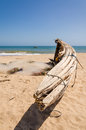 Crude wooden fishing boat lying on yellow beach near Lobito, Angola Royalty Free Stock Photo