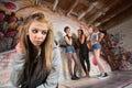 Cruel gang bullies girl unhappy blond near group of teens Stock Photo