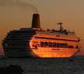 Cruise ship leaving harbor a large at sunset Royalty Free Stock Photo