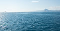 Cruise ship near the horizon with a mountain in the background Royalty Free Stock Photo