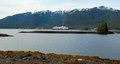 Cruise ship sailing in front of Alaskan mountains during summer