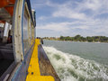 Cruising bumboat through water with distance island Stock Photography