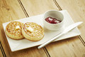 Crumpets toasted on white dish and wooden table top Stock Photo