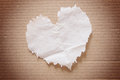 Crumpled brown tissue paper heart shape on cardboard Stock Photo
