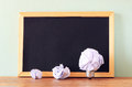 Crumpled paper light bulb metaphor as idea or inspiration and empty black board Royalty Free Stock Photo