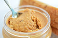 Crunchy peanut butter in jar close up with spoon with slices of fresh bread on white plate in the background concept photo of food Royalty Free Stock Images