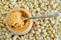 Crunchy peanut butter in jar with spoon with dry roasted peanuts in the background concept photo of food Royalty Free Stock Photo