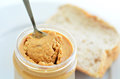 Crunchy peanut butter in jar with spoon with slices of fresh bread on white plate in the background concept photo of food Royalty Free Stock Photo