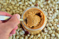 Crunchy peanut butter man hand holds a spoon with in jar with dry roasted peanuts in the background concept photo of food Royalty Free Stock Image