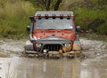 Crush Orange Jeep Rubicon crossing muddy pond Royalty Free Stock Photo