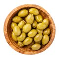 Crushed green olives in wooden bowl isolated on white background. Top view, close-up Royalty Free Stock Photo