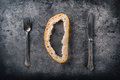 Crust of bread fork and knife on concrete board. Toned image Royalty Free Stock Photo