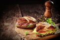 Crusty brown lye bread roll sandwiches with a cheese salami lettuce tomato and cucumber filling on an old grunge board with a Royalty Free Stock Photos