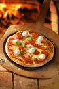 Crusty italian pizza topped with mozzarella high angle view of an uncut cheese and tomato and fresh basil Royalty Free Stock Photos
