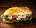 Crusty roll with sliced ham and salad ingredients fresh golden including lettuce tomato onion standing ready prepared for a Royalty Free Stock Images