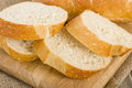 Crusty white bread slices of on a wooden chopping board Royalty Free Stock Photos