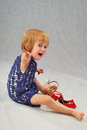 Crybaby crying little girl and red women s shoes Royalty Free Stock Images