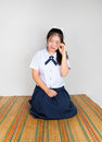 Crying asian thai high school student in sitting with legs folded back to one side Stock Images