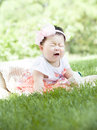 A crying baby an chinese is sitting on grass and Royalty Free Stock Photography