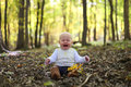 Crying Baby Girl in Autumn Woods under Yellow Maple Trees Royalty Free Stock Photo