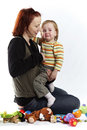 Crying baby loving mother taking care of her little daughter in photo studio is smiling and Stock Image