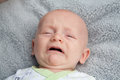 Crying baby with mouth open a a gray blanket in the background Stock Photography