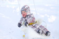 Crying baby on sledge in winter age of year sitting Stock Photography