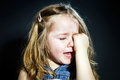 Crying blond little girl with focus on her tears cute dark background Royalty Free Stock Images