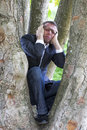 Crying businessman climbing in a tree for mother earth protection