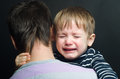 Crying child in the arms of his father Royalty Free Stock Photography
