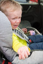 Crying child in car seat little toddler girl a Stock Photography