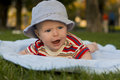 Crying kid baby lies on a tummy outdoors Stock Photos