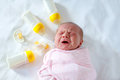 Crying newborn baby girl with nursing bottles. Bottle feeding Royalty Free Stock Photo