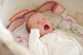 Crying newborn is laying in crib Royalty Free Stock Image