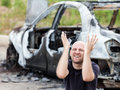 Crying upset man at arson fire burnt car vehicle junk caucasian road wreck accident or wheel Stock Photo