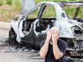 Crying upset man at arson fire burnt car vehicle junk caucasian road wreck accident or wheel Stock Photos