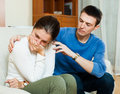 Crying woman has problem man consoling her women men on sofa at home Stock Photos