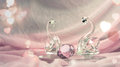 Crystal or glass swans with a diamond on pink cloth Royalty Free Stock Photo