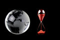 Crystal globe and red hourglass on black background conceptual image Royalty Free Stock Image