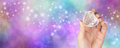 Crystal healing website banner with glitter female therapist holding a clear quartz puff heart tumbled stone in hand on a Stock Images
