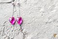 Crystal heart shaped earrings gorgeous pink on stone background Stock Photography