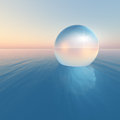 Crystal sphere floating sunrise a surreal over the ocean horizon on clear morning sky Royalty Free Stock Photography