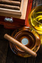 Cuban cigar in ashtray with glass of cognac ad humidor Royalty Free Stock Photo