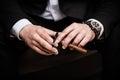 Cuban cigar elegant man wearing black suit and white shirt cut indoor shot closeup Royalty Free Stock Images