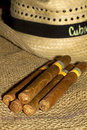 Cuban cigars black and white straw hat on burlap Royalty Free Stock Image