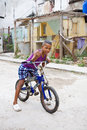 Cuban kid on bike a mulatto boy a in the historic center of havana cuba Royalty Free Stock Photos
