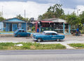Cuban old cars parked in highway private restaurant-Cuba Royalty Free Stock Photo
