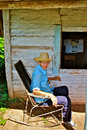 Cuban peasant in rocking chair with straw hat sitting a worn front of his very simple wooden cabin rural cuba Royalty Free Stock Images