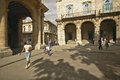 A cuban woman and child walking through an old plaza in old havana cuba with archways Royalty Free Stock Image